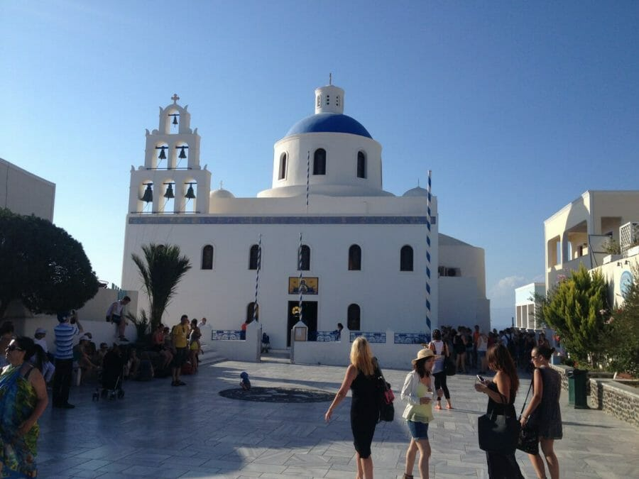 people walking at the main square of Oia, Santorini, and a blue-domed church with white walls in the background