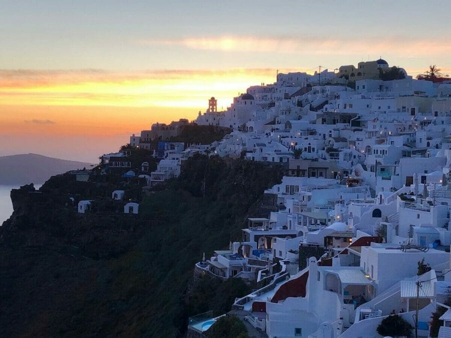 Whitewashed houses on the top of a cliff in the village of Imerovigli, Santorini, during the sinset