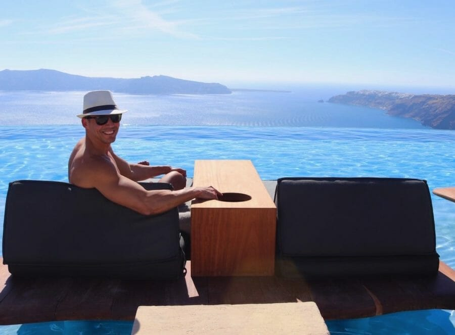Pericles Rosa wearing a white hat and sunglasses sitting on a lounge chair by an infinity swimming pool with the Aegean Sea in the background at Cavo Tagoo Santorini