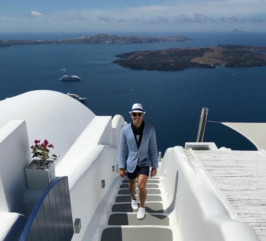 Pericles Rosa wearing a white hat, sunglasses, light blue blazer, marine blue scarf and shirt, white t-shirt and sneakers walking up the stairs of Chromata Hotel in Santorini.