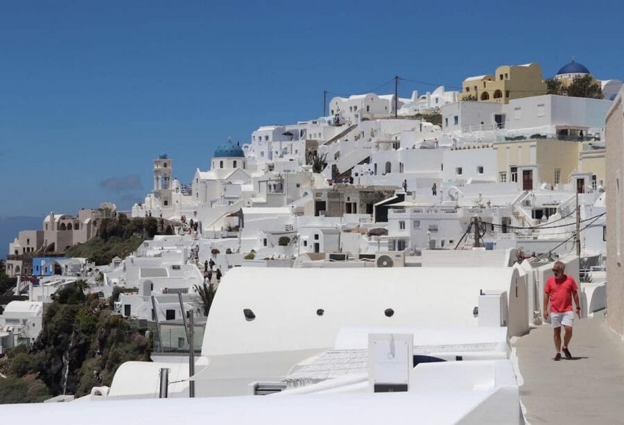 A man wearing a light red t-shirt and beige short walking on a path in the village of Imerovigli, Santorini, with several whitewashed houses and a blue-domed church surrounding him