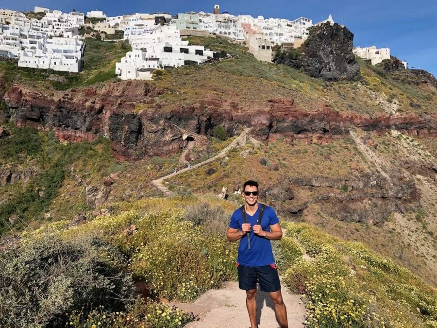 Pericles Rosa wearing a blue t-shirt, blue short and sunglasses hiking Skaros Rock and whitewashed houses of the village of Imerovigli, atop of a colossal red cliff covered low vegetation behind him
