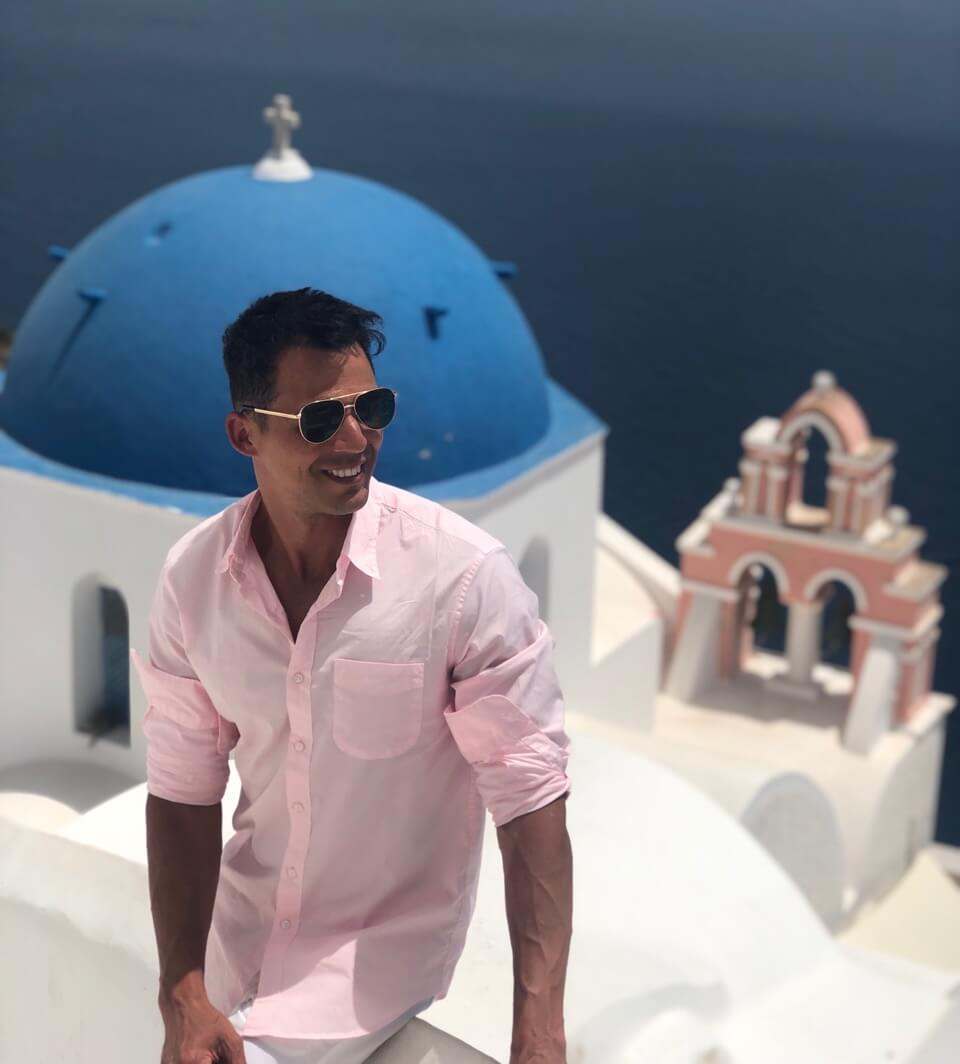 Pericles Rosa wearing sunglasses and a light pink shirt sitting on a white wall, a blue-domed church and a salmon bell tower behind him, in the village of Oia, Santorini