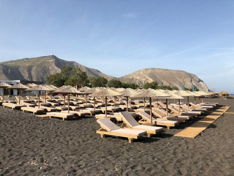 lounge chairs and umbrellas on the Perissa Beach, Santorini, and Mesa Vuono Mountain in the background