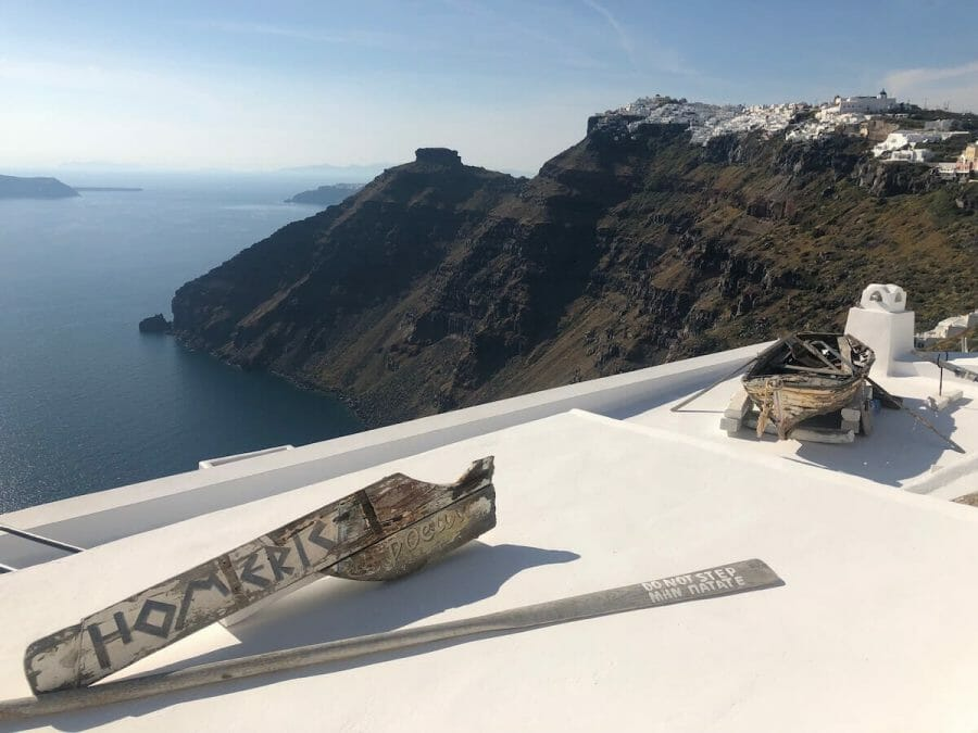 An old wooden boat on the rooftop of  Homeric Hotel Santorini, and the whitewashed houses of the villages of Firostefani and Imerovigli and the Agean Sea in the background