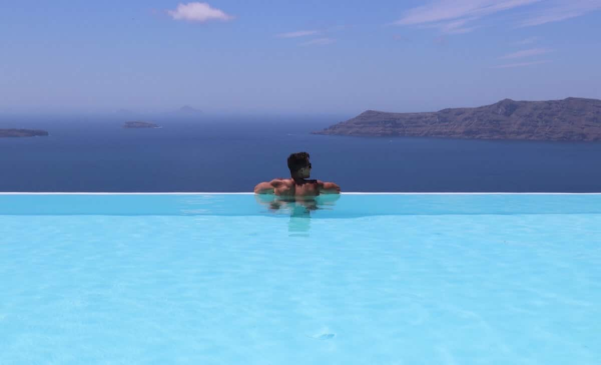 Pericles Rosa standing inside an infinity swimming pool with the Aegean Sea in the background at CSky Luxury Hotel in Santorini