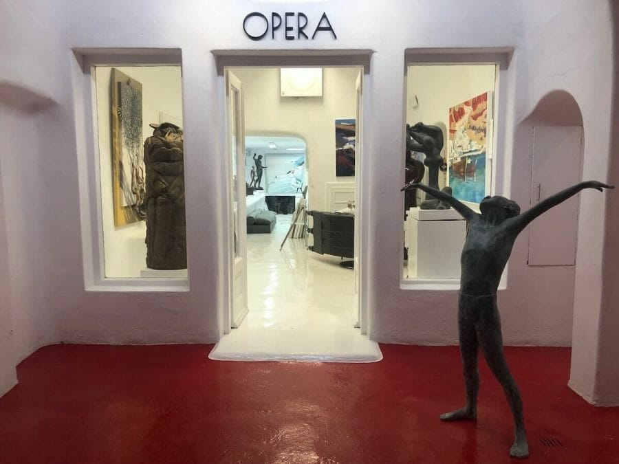 A statue at the entrance of Opera Art Gallery in Oia, Santorini, and other several artworks inside the gallery in the background