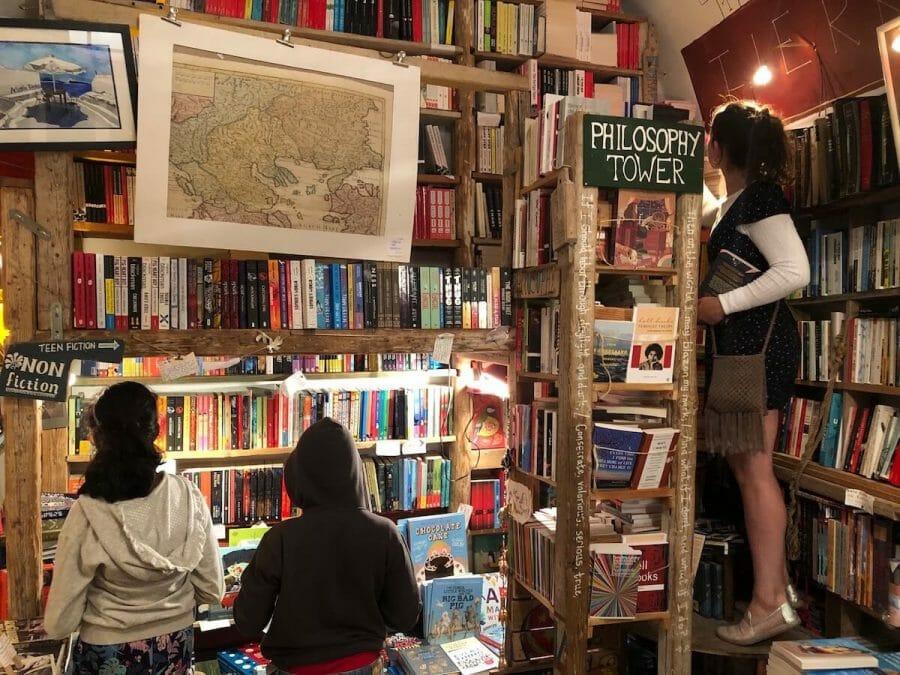 Three people among books on the shelves at Atlantis Bookshop, Oia, Santorini