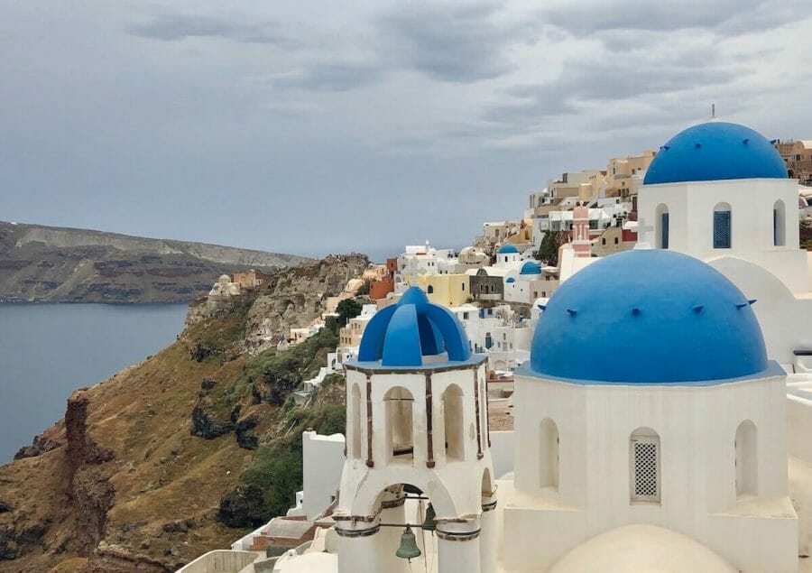 The famous three blue-domed church and house of the top of the cliff in the village of Oia, Santorini