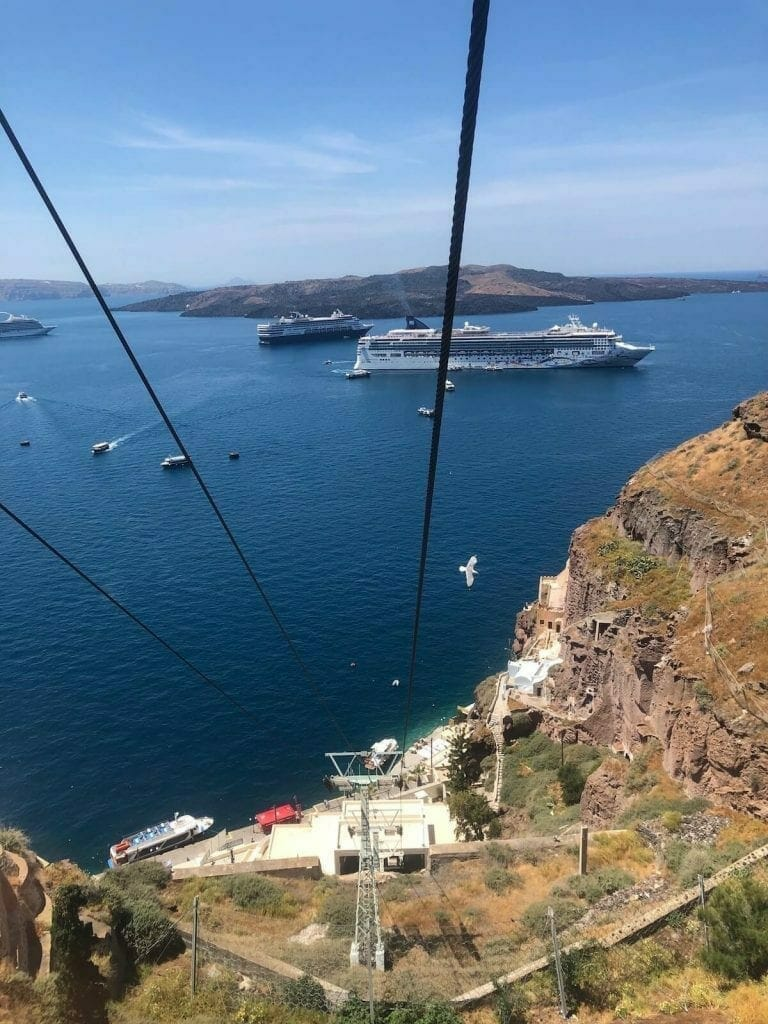 The view of two cruise ships, Nea Kammeni Island and the Aegean Sea from a Santorini's cable car