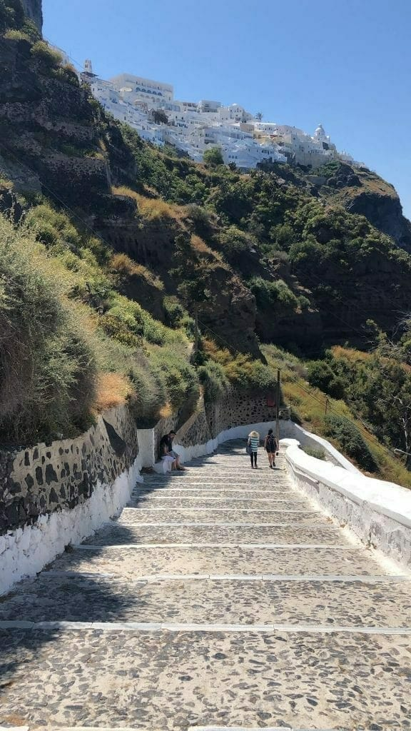 Two people walking down the 587 steps to Santorini old port