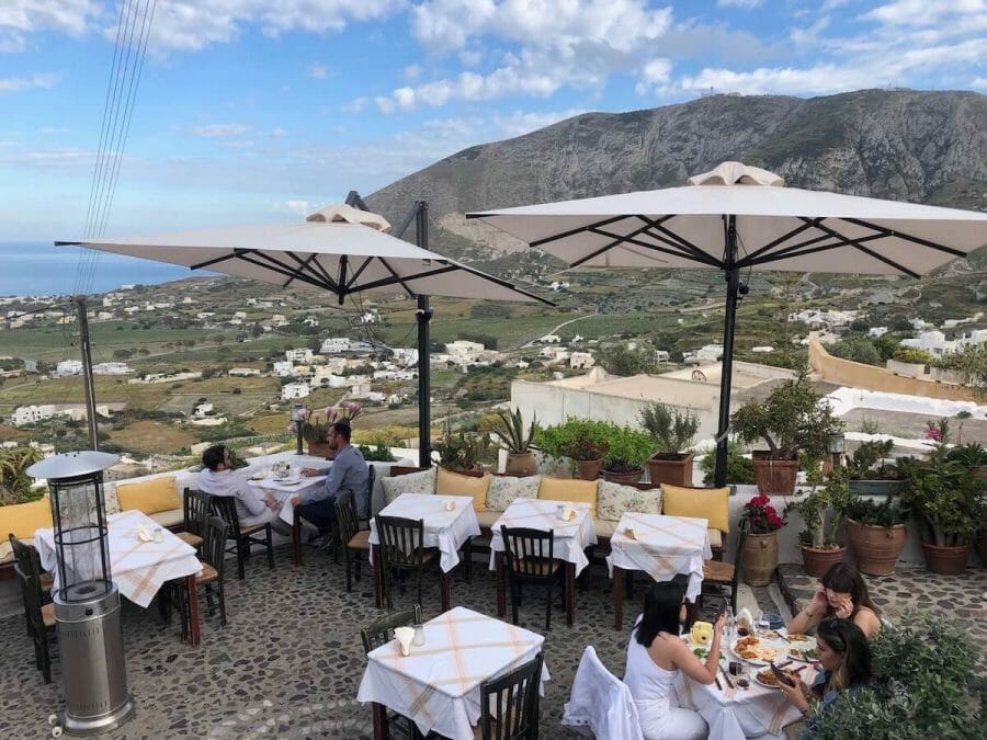 five people eating on the outside seating of Metaxi Max Restaurant, Santorini, which has white umbrellas, tables, chairs and some plants
