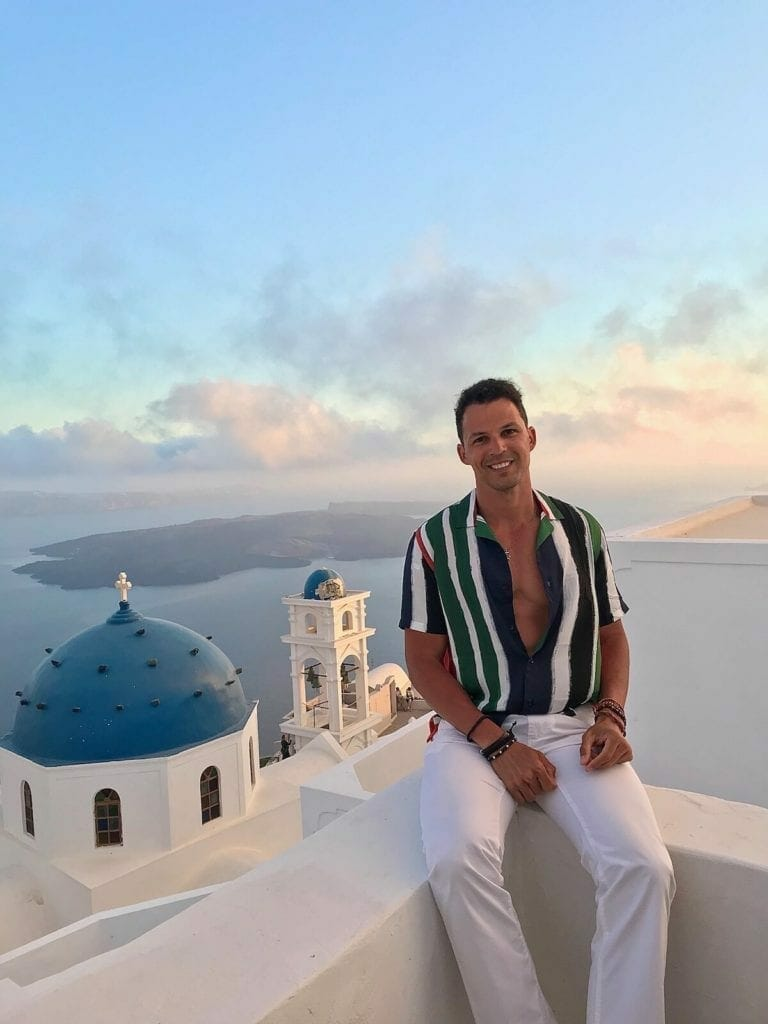 Pericles Rosa wearing a striped shirt and white trouser sitting on a white balcony in the village of Imerovigli, Santorini, and ti the background the Anastasi Church, Nea Kammeni island and the Aegean Sea