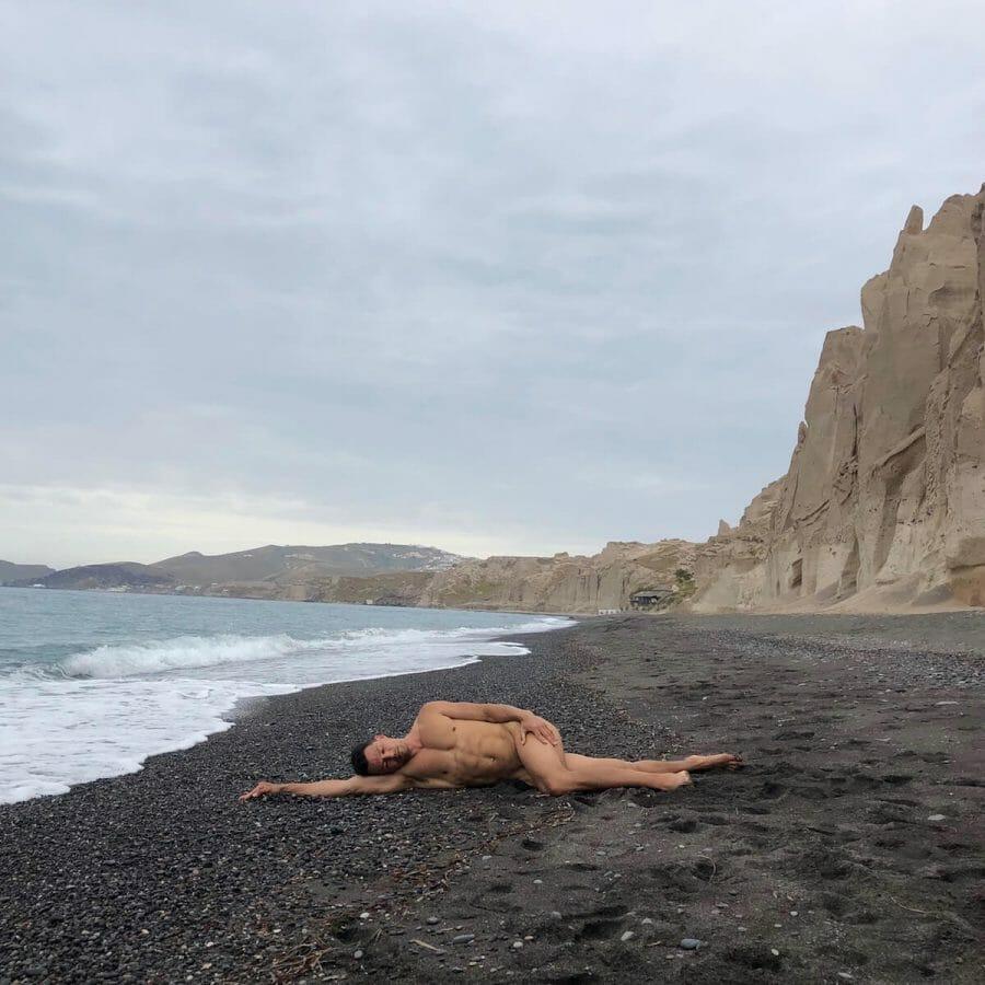 A man laying down on the black sand of Vlichada Beach, Santorini