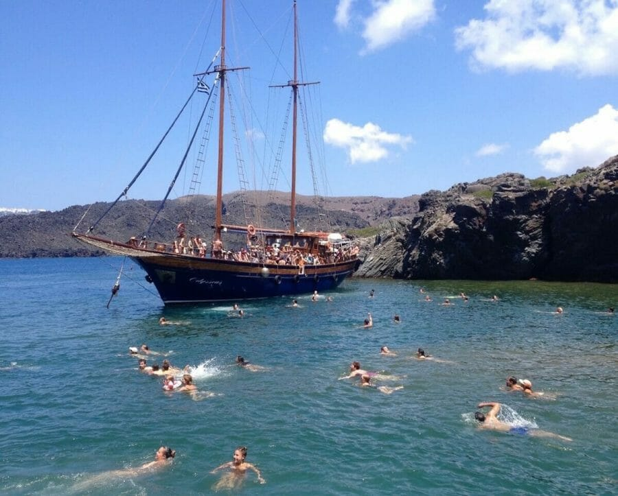 people swimming on a hot spring in Santorini and others on a boat during a caldera tour