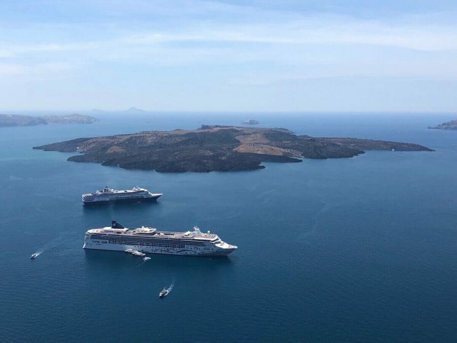 Two cruise ships sailing in the Aegean Sea near the island of Nea Kameni, Santorini, Greece