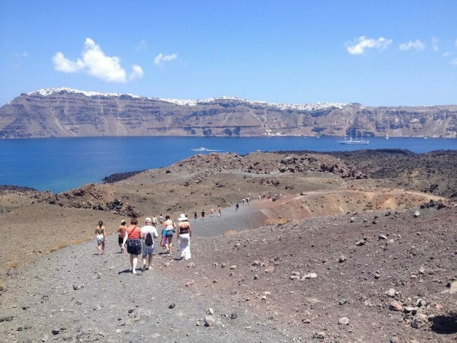 people walking at Nea Kameni Volcanic Park, which has black sand and volcanic rocks, and the island of Santorini with whitewashed houses atop of an immense cliff in the background