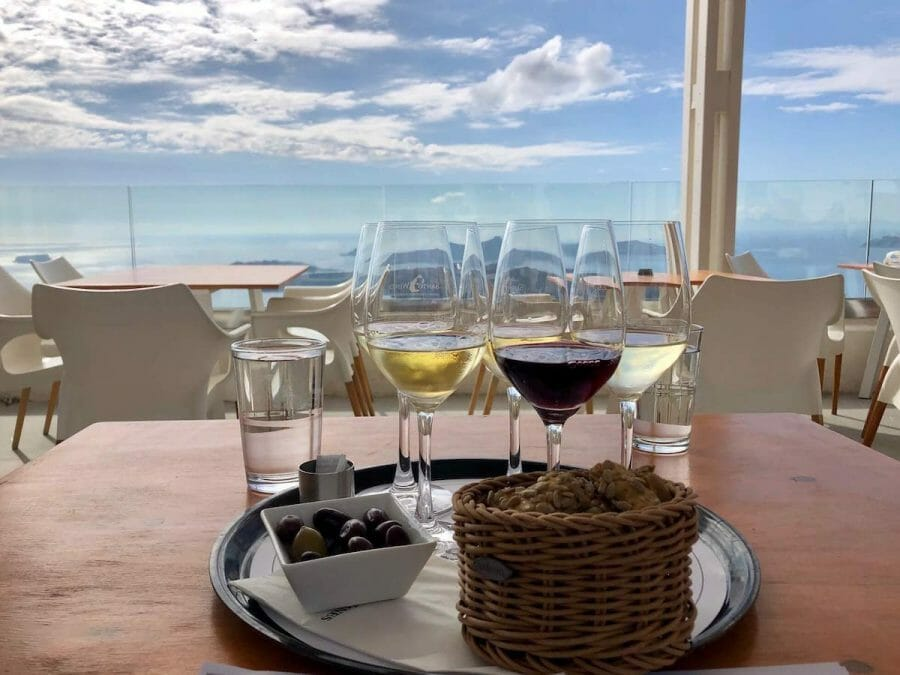 a trail with four glasses with some red and white wine, a basket with some bread and a white bowl with olives served during a wine tasting at Santo Wines, Santorini